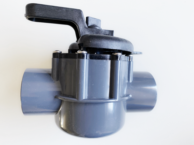 Gray two way valve against a white background.