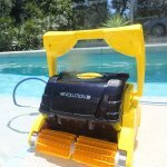 Revolution robotic pool cleaner next to swimming pool.