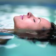 Woman at the spa relaxing at the swimming pool floating with eyes closed