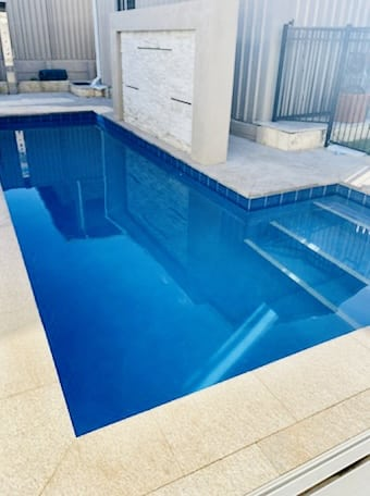 Clear aqua blue swimming pool which is being heated shallow side view.