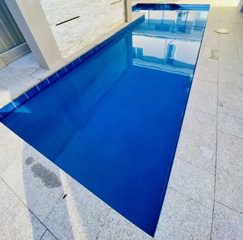 Clear aqua blue swimming pool which is being heated.